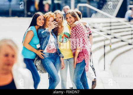 Groupe de quatre amies en tenant un smartphone avec selfies Banque D'Images