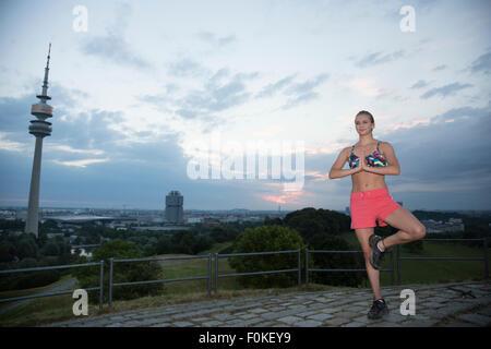 Allemagne, Munich, young woman practicing yoga sur une colline dans le matin Banque D'Images