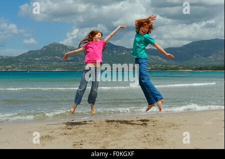 France, Corse, Calvi , deux enfants sautant en l'air sur la plage Banque D'Images