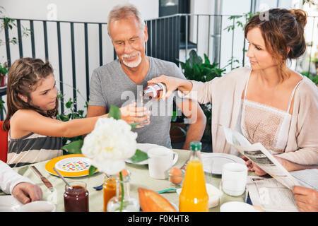 Trois générations de la famille assis à une grande table de petit déjeuner sur le balcon Banque D'Images