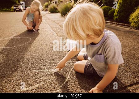 Les enfants en utilisant des craies de trottoir dans leur quartier Banque D'Images