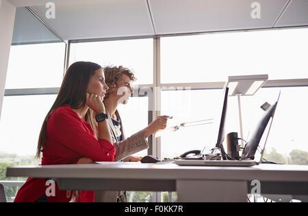 L'homme et de la femme à l'écran de l'ordinateur au bureau de Banque D'Images