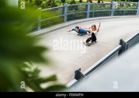 Jeune couple enthousiaste équitation descente avec planches à roulettes Banque D'Images
