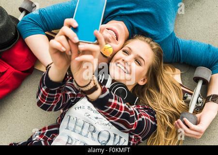 Happy young couple étendue sur le sol avec de la planche à roulettes Banque D'Images