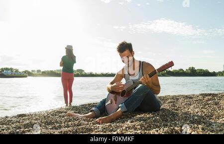 Jeune homme jouant de la guitare avec femme par le Riverside Banque D'Images