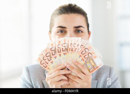 Femme cachant son visage derrière le ventilateur de l'argent euro Banque D'Images