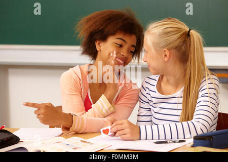 Deux filles murmurer sur une lettre d'amour