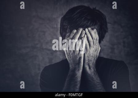 Le chagrin, l'homme qui couvre le visage et de pleurer, image monochromatique Banque D'Images