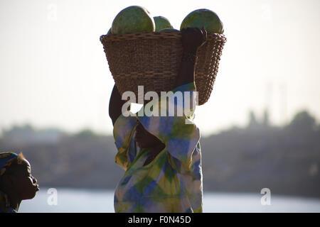 Femme non identifiée portant des légumes sur sa tête dans les rues de Mopti avec une jeune fille Banque D'Images