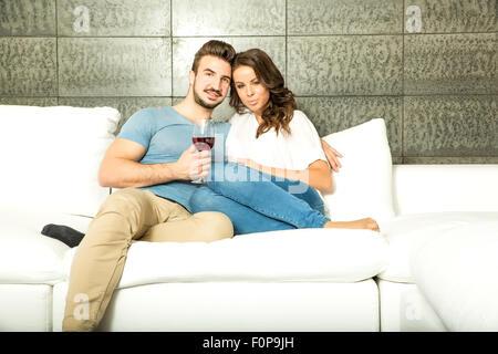 Un jeune couple dans le salon, buvant un verre de vin rouge sur le canapé. Banque D'Images