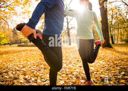 Détail de l'homme et de la femme s'étend les jambes avant de jogging en automne nature Banque D'Images