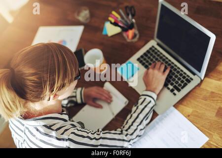 Jeune femme entrepreneur travailler assis à un bureau en train de taper sur son ordinateur portable dans un bureau à la maison, vue de dessus