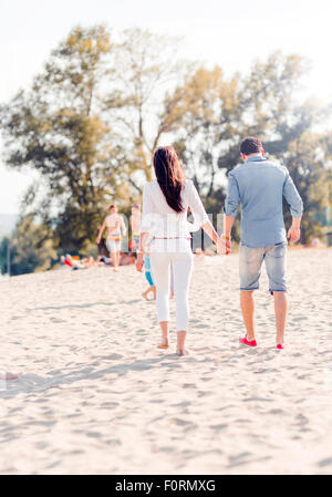 Couple holding hands and walking on a sandy beach Banque D'Images