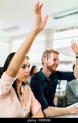 Belle jeune femme et un homme les mains dans la salle de classe tout en restant assis à un bureau Banque D'Images