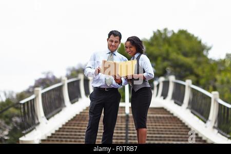 Les gens d'affaires debout devant des escaliers à la paperasserie, à smiling Banque D'Images