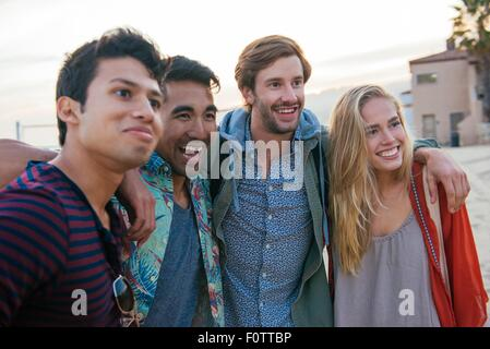 Groupe d'amis Standing together on beach, rire Banque D'Images