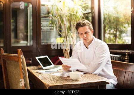 Jeune chef assis à travailler à la paperasserie à Banque D'Images