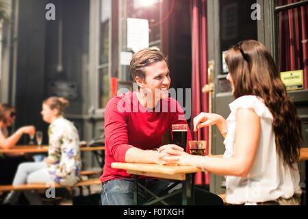 Couple assis face à face à beer garden holding hands Banque D'Images