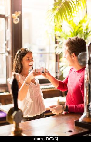 Couple un toast tenue shot glasses Banque D'Images