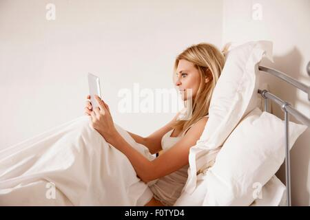 Mid adult woman sitting up in bed using digital tablet