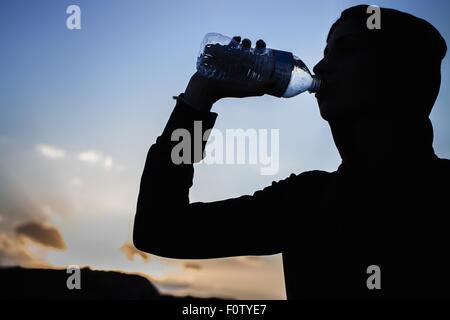 Jeune femme à boire de l'eau bouteille Banque D'Images