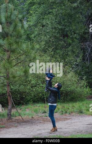 Mid adult woman holding up toddler fille sur chemin forestier, Yosemite National Park, California, USA Banque D'Images