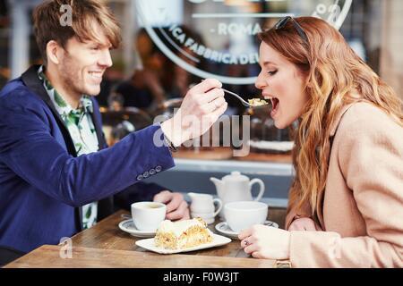 Gâteau à l'alimentation de l'homme petite amie at sidewalk cafe, London, UK Banque D'Images