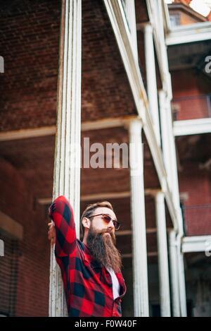 Homme avec barbe, appuyé contre un pilier Banque D'Images
