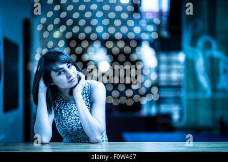 Attendre que quelque chose ou quelqu'un: une jeune femme assise seule dans un café bar UK (floue) bokeh background Banque D'Images