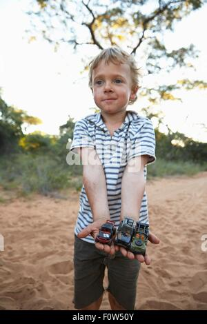 Portrait of young boy holding toy cars, Grootfontein, Kavango, Namibie Banque D'Images