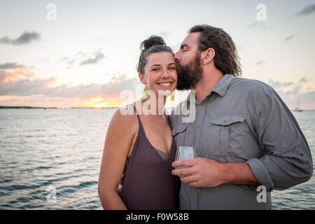 Man kissing petite amie sur la joue à l'autre, Islamorada, Florida, USA Banque D'Images