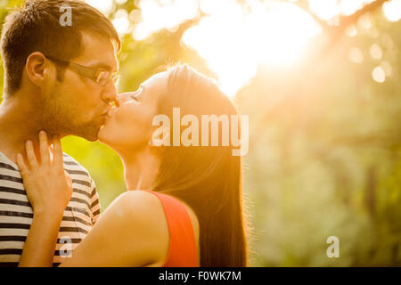 Couple romantique au coucher du soleil et l'embrasse dans la nature Banque D'Images