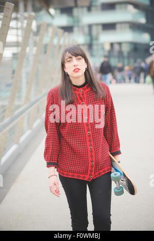 Belle jeune femme de race blanche en se promenant dans les rues de la ville avec une planche à roulettes à poser et à la jeunesse, à huis clos -
