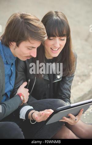 Couple de jeunes beaux caucasian man et woman business 10 lit assis sur un trottoir de la ville à l'aide d'une tablette Banque D'Images