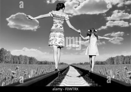 Mère avec la fille, rendez-vous sur rails, un retour à une caméra, dans le champ, à l'été Banque D'Images