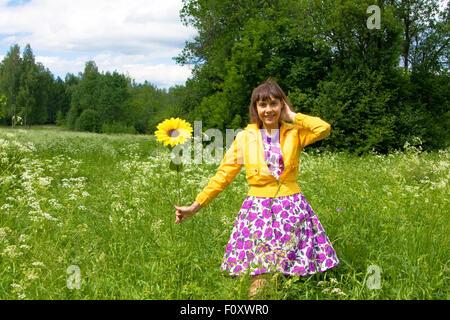 Jeune femme, caucasien, brunette, avec le tournesol en parc. Banque D'Images