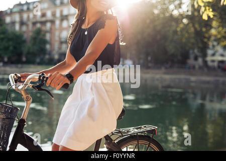Cropped shot of young woman cycling par un étang. Femme un jour d'été équitation son vélo.