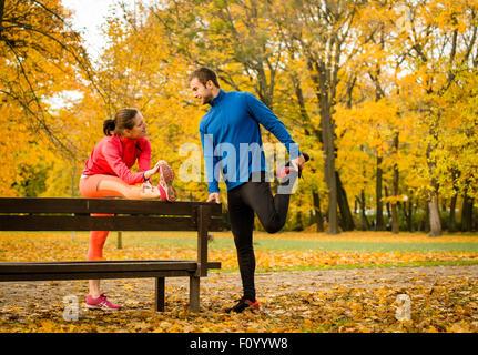 Jeune couple stretching muscles sur banc avant de jogging en automne nature Banque D'Images