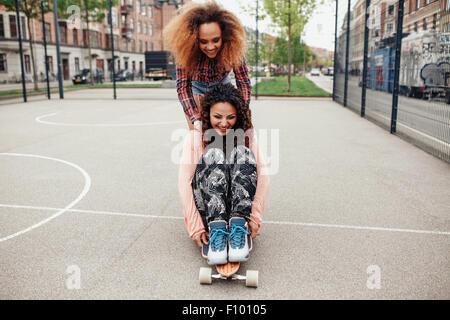Femme poussant son ami sur longboard. Les filles en patinage de Hipster un terrain de basket dans la ville. Banque D'Images