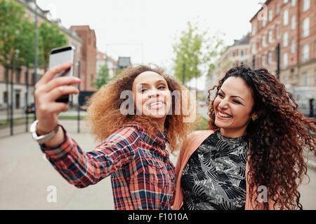 Deux belles jeunes femmes de prendre une photo ensemble sur la rue de la ville. Young female friends prenant un Banque D'Images