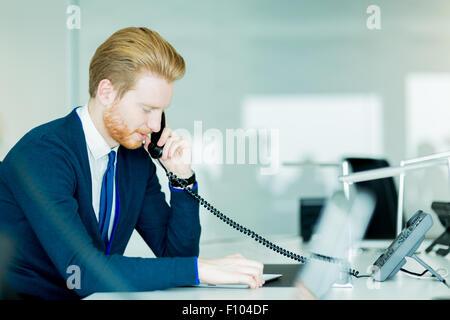Un beau mâle, red haired travailleur dans un centre d'appel de bureau Banque D'Images
