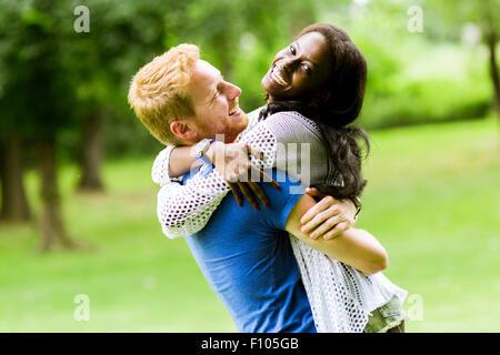 Portrait d'un couple heureux de danser et s'étreindre dans un parc en plein air Banque D'Images