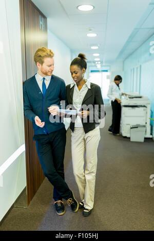 Deux jeunes gens d'affaires de discuter des idées sur un couloir de bureau tout en maintenant une tablette