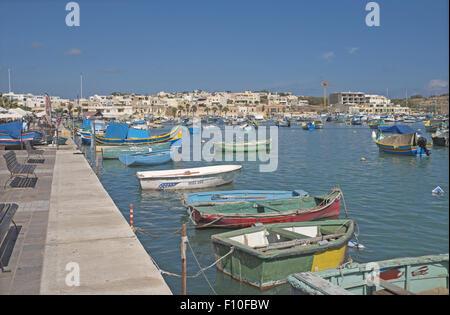 Peint aux couleurs vives des bateaux de pêche traditionnels dans le port, village de pêcheurs de Marsaxlokk, Malte. Banque D'Images