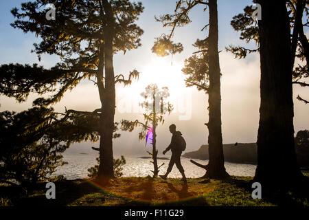 Caucasian hiker walking near ocean Banque D'Images