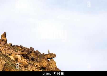 Caucasian hiker debout sur falaise boulder, Smith Rock State Park, Oregon, United States