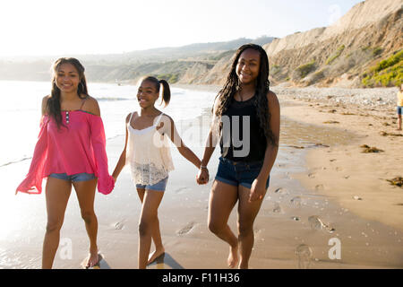 African American sisters holding hands on beach