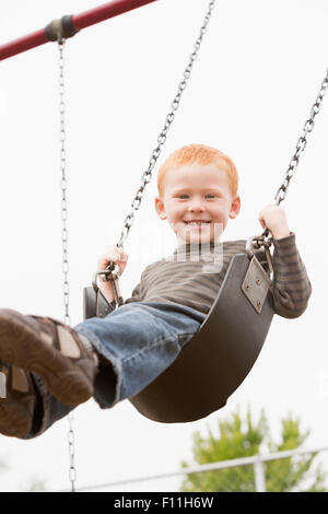 Young boy sitting on swing aire Banque D'Images