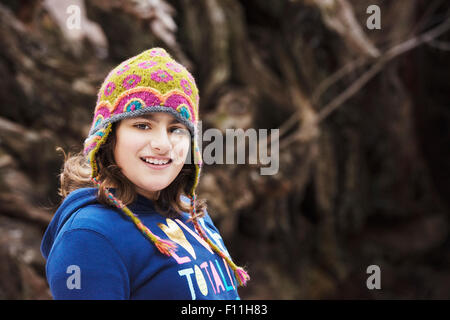 Mixed Race girl wearing knit cap in forest Banque D'Images