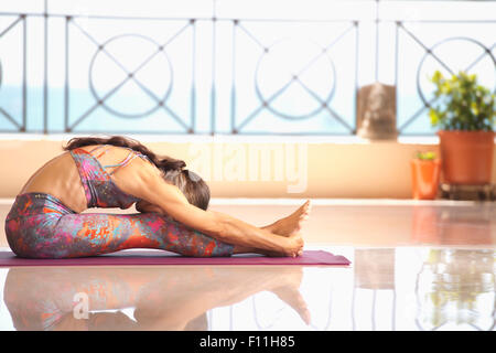 Hispanic woman practicing yoga on balcon Banque D'Images